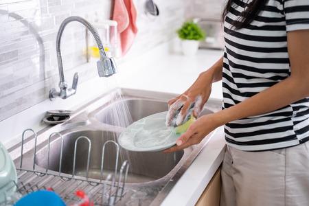 laver une assiette à la main sur un évier