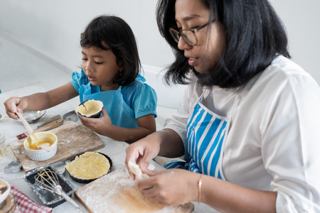 mother and kid learning to make some dough