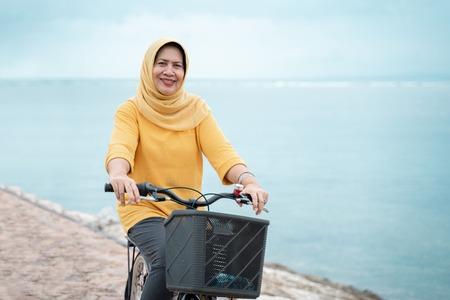 happy senior muslim female riding a bicycle