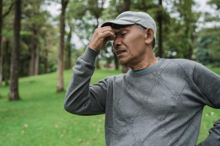 Senior asiatischer Mann mit Kopfschmerzen Standard-Bild