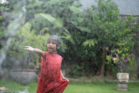 kid enjoying playing with water splash in garden