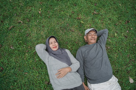 senior asian muslim couple laying down on grass