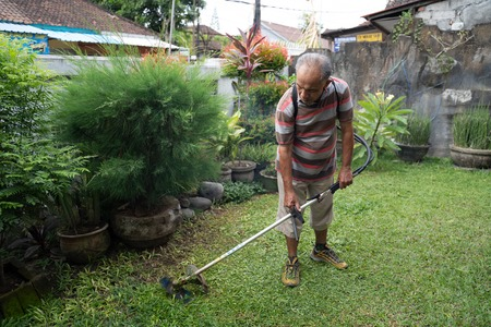 senior asian man mowing grass at his own home garden