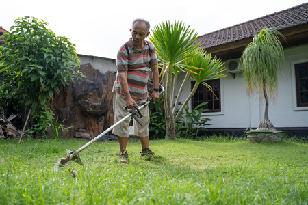 old asian man mowing his garden Stock Photo