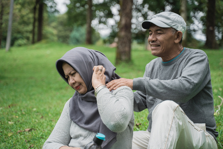 senior male couple giving some massage on shoulder and neck to his wife Stock fotó