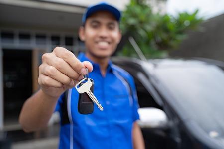 mechanic holding car key and smiling Stock Photo