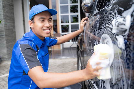 male car cleaning service worker washing black car