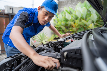 mechanic doing some inspection on cars engine