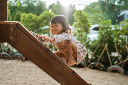 a girl enjoy playing on the wooden board climb alone