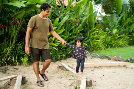a patiently father helps his little girl when walking on the balance beam