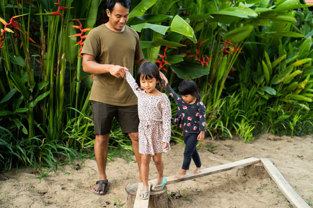 portrait a father helping two daughter with holding his hands when playing balance beam