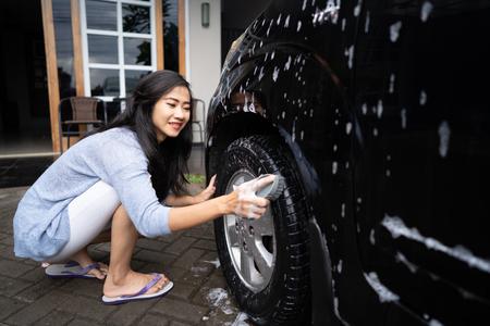 asian woman washing her car