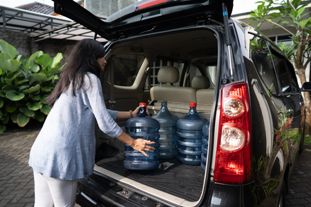 woman put water gallon in the car trunk Stockfoto