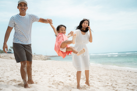 father and mother swinging a little girl on the beach
