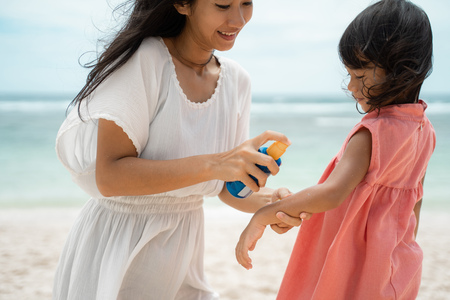 application sunblock to daughter skin before playing on the beach