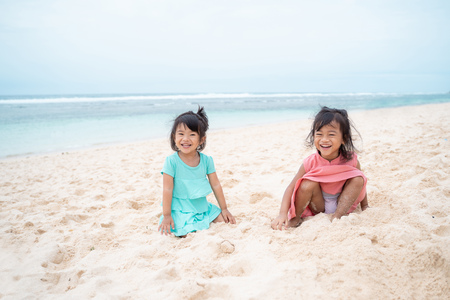 two daughter sit down on white sand smiling