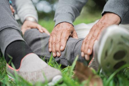seniors hand giving massage on leg Stock Photo