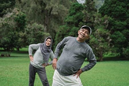 due anziani e una donna che fanno un po' di stretching Archivio Fotografico