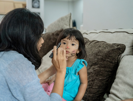 asian mother face painting her little daughter Stock Photo - 116802197
