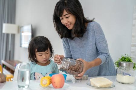 madre preparando el desayuno para sus hijas Foto de archivo