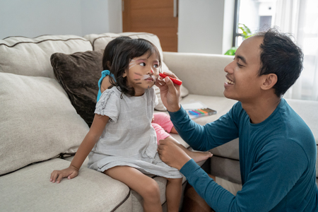 dad making some face painting on daughters faces