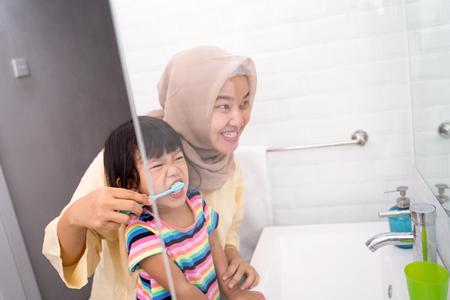 mom brush her kids teeth Stock Photo