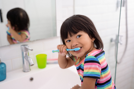 asian little girl brushes her teeth and her head looks when called by her mother Imagens