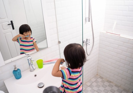 asian little girl brushes her teeth alone in the bathroom