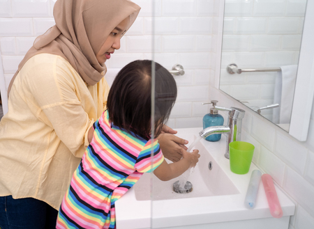 mom help her kid to wash her hands