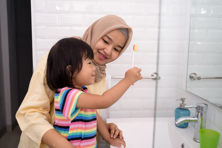 mother and her daughter brushing teeth