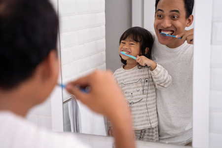 father and daughter brushing teeth together Banque d'images - 116841120