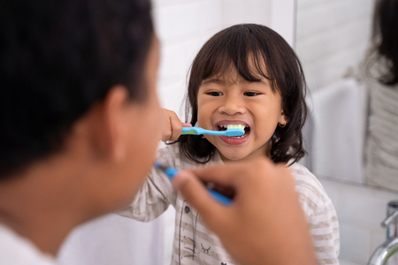 kid and dad having fun while brushing their teeth