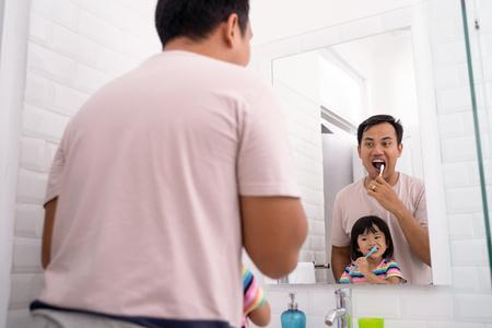girl brushing teeth in bathroom sink with dad