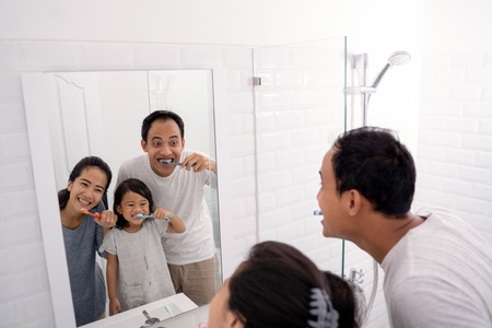 happy asian family brush their teeth together
