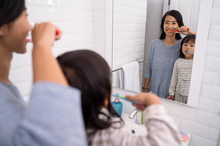 mother and daughter brushing teeth in the bathroom sink Stock Photo