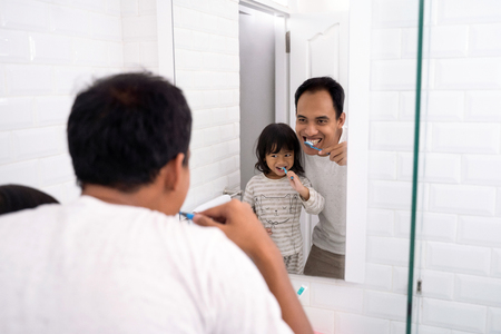 father and daughter brushing teeth together Banque d'images - 116841160