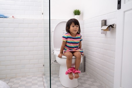 Niño asiático sentado en el inodoro con pantalones bajados Foto de archivo