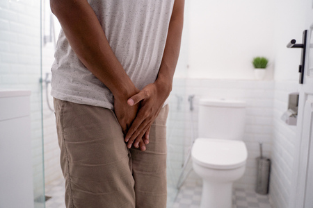 man hold his genitals in the toilet before peeing
