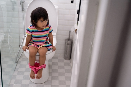 asian toddler sitting on toilet with pants down