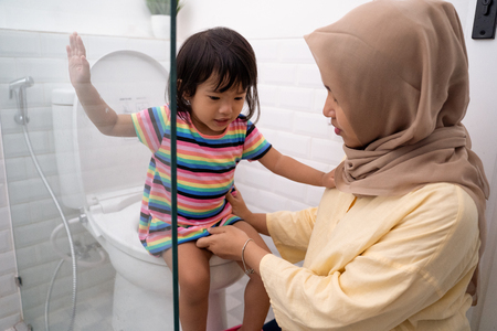 mother help her daughter to sit on the toilet