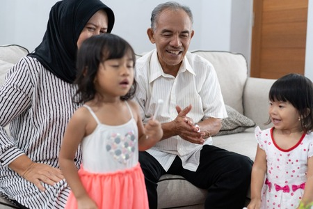 Grandpa happiness by clapping his hands while playing with two grandchildren 写真素材
