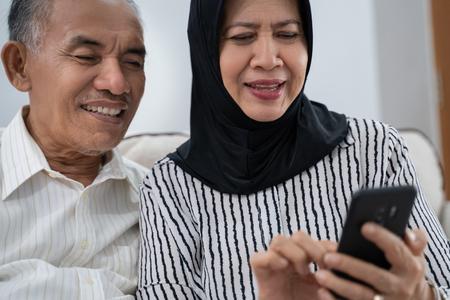 mature asian couple using smartphone
