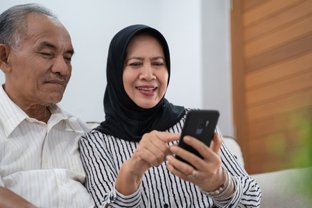 mature asian woman and man using cellphone