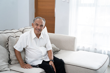 portrait of a grandfather alone sitting on the couch look at camera