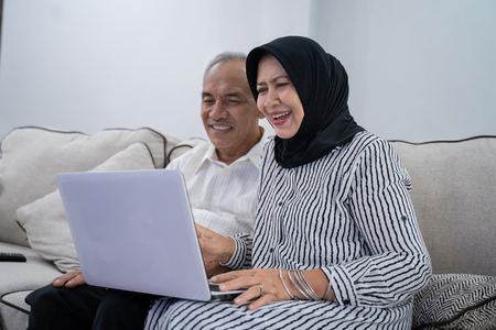 pareja de ancianos asiáticos juntos usando laptop