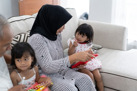 Asian Muslim grandmother explained how to play the xylophone instrument to her granddaughter