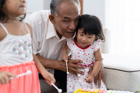 portrait of grandfather encouraging his granddaughter to play the xylophone 写真素材