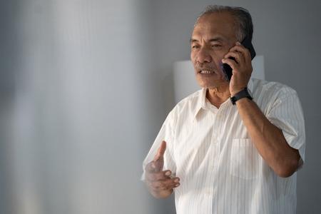 een ervaren zakenman die telefonisch met een smartphone praat in tweerichtingscommunicatie Stockfoto