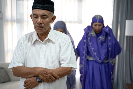 portrait of family members praying in congregation at the prayer room