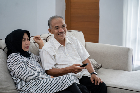 asian muslim couple mature sitting couch relaxed when enjoy television